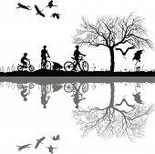 Family cycling on the edge of the lake