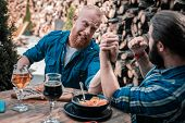 Bearded Men Arm Wrestling While Drinking Beer Together poster