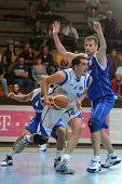 KAPOSVAR, HUNGARY - OCTOBER 15:Jozsef Lekli (in white) in action at a Hugarian National Championship basketball game Kaposvar (white) vs. Jaszbereny (blue) on October 15, 2011 in Kaposvar, Hungary.