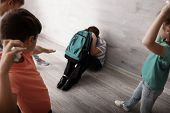 Children bullying little boy with backpack indoors poster