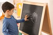 Little boy putting his palm on drawing at child psychologists office. Autism concept poster