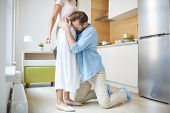 Young knelt apologizing man embracing his wife and begging her not to leave poster