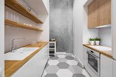 Small, Functional Kitchen With Wooden Countertop And Hexagonal Floor Tiles poster