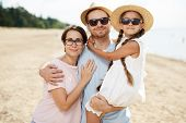 Affectionate family of father, mother and little daughter embracing while enjoying summer weekend on poster