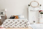 Lamp On Desk Next To Patterned Bed With Pillows In White Bedroom Interior With Mirror. Real Photo poster