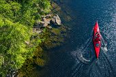 River Kayaker Aerial View. Caucasian Sportsman In The Red Kayak Paddling On The Scenic River Along T poster