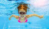 Smiling little girl in swim goggles swimming underwater in pool. Teenage girl diving underwater poster