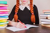 Redhead School Girl In School Uniform Sits At Desk On Gray Background. Colored Text Books On Table.  poster