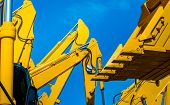 Yellow Backhoe With Hydraulic Piston Arm Against Clear Blue Sky. Heavy Machine For Excavation In Con poster
