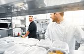 cooking food, profession and people concept - happy male chef and cook at restaurant kitchen poster
