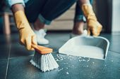 Young Woman In Gloves Sweeping Floor With Brush. Closeup Of Girl Wearing Protective Gloves Swiping F poster
