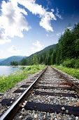 image of train track  - Train tracks near a large lage going through the mountains - JPG