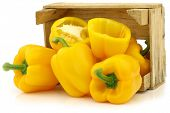 fresh yellow bell peppers (capsicum) and a cut one in a wooden crate on a white background