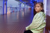 Little girl sitting on bench on deck of large passenger ship