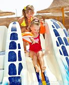 Little girl on water slide at aquapark. Summer holiday.