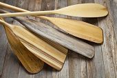 pile of wooden canoe paddles with different shapes and sizes of blades against grained wood deck