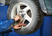 mechanic technician worker installing car wheel at maintenance and repair auto service station