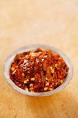 Hot Red Chilli Chillies pepper crushed in tin bowl on wood