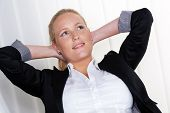 stock photo of whip-hand  - a pensive business woman sitting on her chair with his hands behind his head - JPG