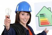 Mujer que sostiene el cartel de calificación energética y bombilla