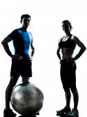 one caucasian couple man woman personal trainer coach exercising fitness ball silhouette studio isol