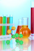Molecule model and test tubes with colorful liquids on blue background
