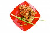 savory food : roasted chicken legs garnished with green sprouts and peppers on red plate isolated ov