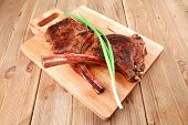 meat savory : roasted beef ribs served with green chives over black table