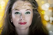 Portrait Of Beautiful Girl With A Gold Branch In Hair With Lens Flare Behind