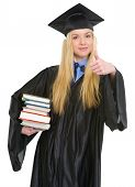 Happy Young Woman In Graduation Gown Showing Books And Thumbs Up