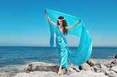 Water Nymph. Beautiful Woman In Blue Chiffon Dress Embracing Over Blue Sky On Beach