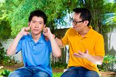 Chinese Asian father talking to his son but he will not listening, holding his ears with his hands r