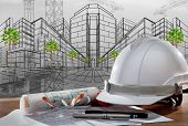 picture of industrial safety  - file of safety helmet and architect pland on wood table with sunset scene and building construction - JPG