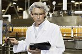 Man looking at tablet PC while working in bottling factory