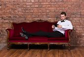 Businessman Lying On A Settee And Reading Tablet