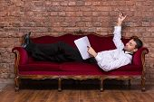 Businessman Lying On A Settee And Reading Paperwork