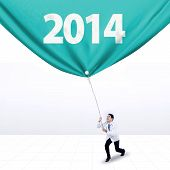 stock photo of pulling  - Young male doctor is pulling banner of new year 2014 - JPG