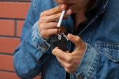 picture of cigarette lighter  - A smoker with a cigarette and a lighter - JPG
