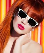 Colorful summer portrait of an attractive young woman with sunglasses