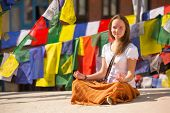 Girl sitting on Buddhist stupa, prayer flags flying in background.