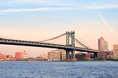 Manhattan Bridge over East River viewed from New York City Lower Manhattan waterfront at sunset.