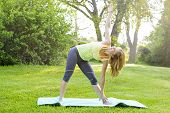 picture of extend  - Female fitness instructor doing yoga extended triangle pose outdoors in green park - JPG
