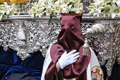 Nazarene that goes with the hand on the manigueta the throne in a procession of holy week