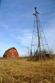 The old windmill water tower dwarfs the deserted barn