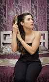 stock photo of gril  - vintage vignetting combing hair gril portrait in bedroom - JPG
