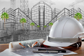 stock photo of land development  - file of safety helmet and architect pland on wood table with sunset scene and building construction - JPG