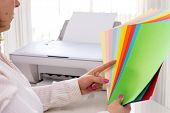 Woman selects color of paper for printer.