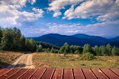 Empty wooden terrace with mountain landscape in the background