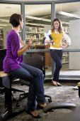 Two female university students talking in library