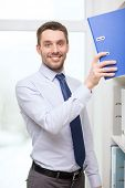 business and office concept - handsome businessman picking folder at office